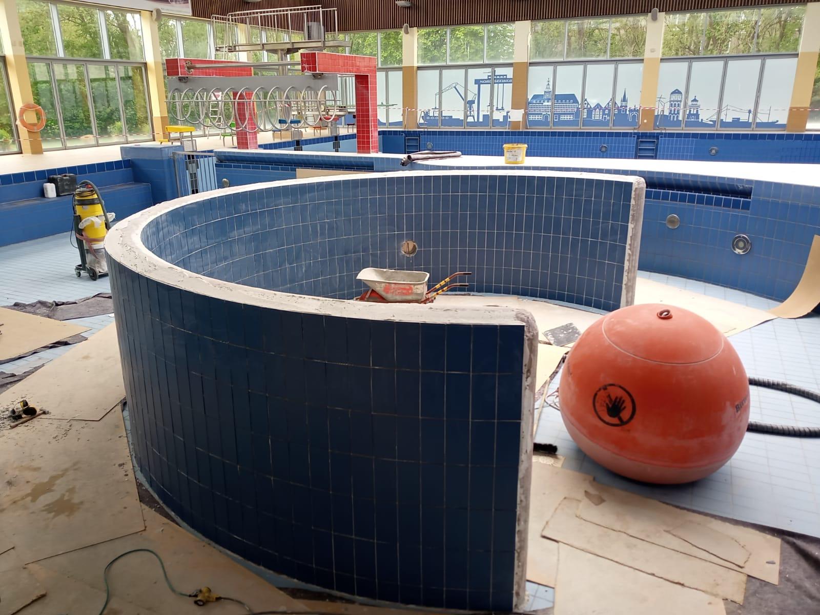 Firma Isenburg verfugt die neu verlegten Fliesen rund um den Wellenball